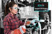 Young female farmer use Ar glasses artificial intelligence adviser to fix industrial machine and holding open end wrench with graphic. Augmented reality glasses technology , industry 4.0 concept.