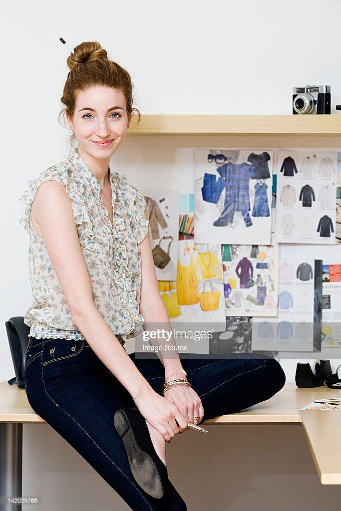 Young female fashion designer sitting on desk, portrait : Stock Photo