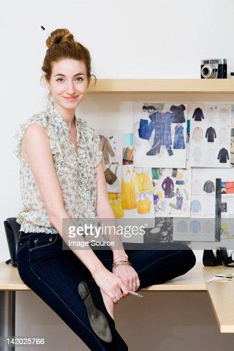 Young female fashion designer sitting on desk, portrait