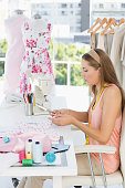 Side view of a young female fashion designer working on fabrics in the studio