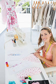 High angle portrait of a young female fashion designer working on fabrics in the studio
