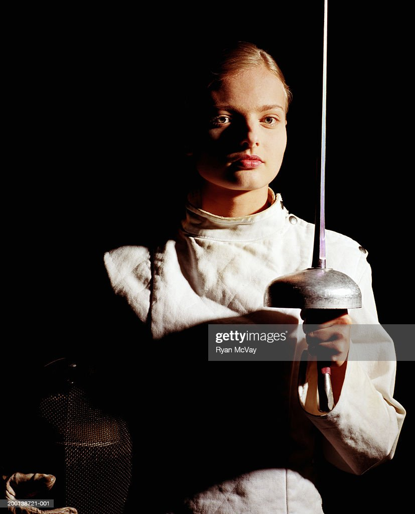 Young female fencer holding foil and fencing mask, portrait : Stock Photo