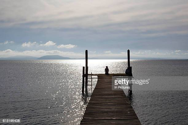 Young female figure silhouette sitting on the end of a jetty on the banks of a lake at dawn showing vanishing point Working Gaucho Fazenda in Rio...