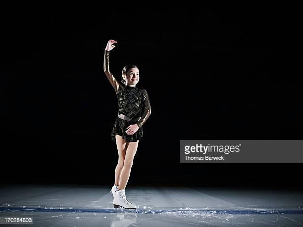 Young female figure skater finishing performance
