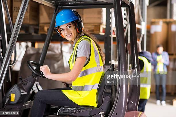 Junge weibliche Fahrer in einem Lager Gabelstapler