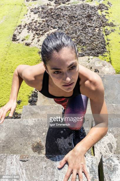 Young female free runner climbing up sea wall