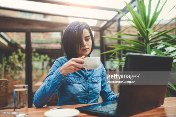 Young Female Freelancer Working on Laptop Computer in a Cafe