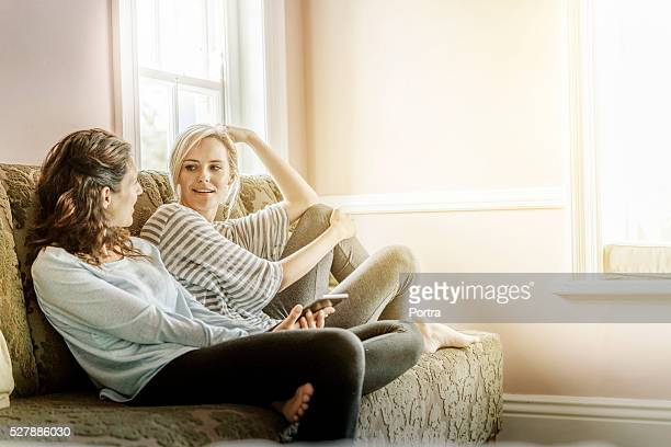 Young female friends gossiping on sofa at home