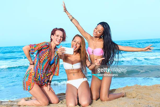 Young female friends making selfie on the beach