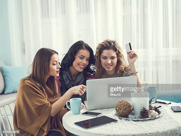 Young female friends shopping together from home.