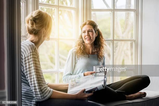 Young female friends talking on window sill
