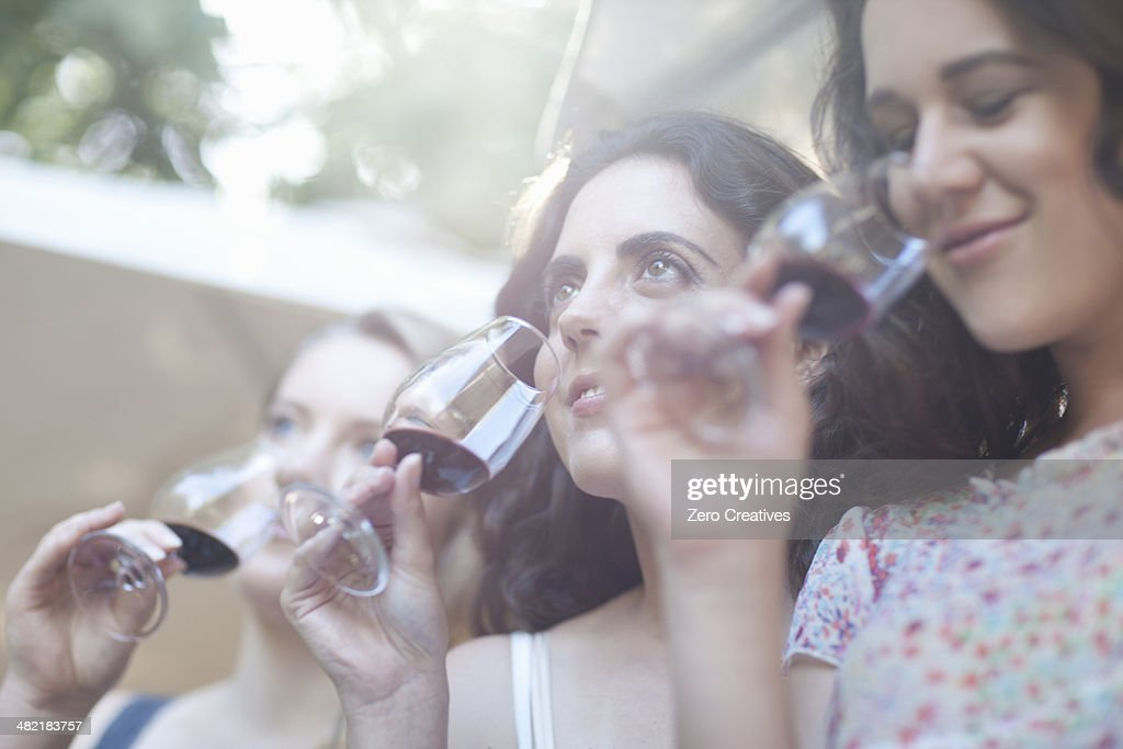 Young female friends tasting and smelling wine at vineyard