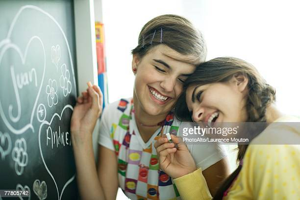 Young female friends writing names in hearts on chalkboard, laughing