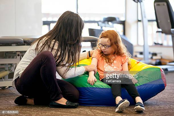 Young female girl gets assistance from a female therapist