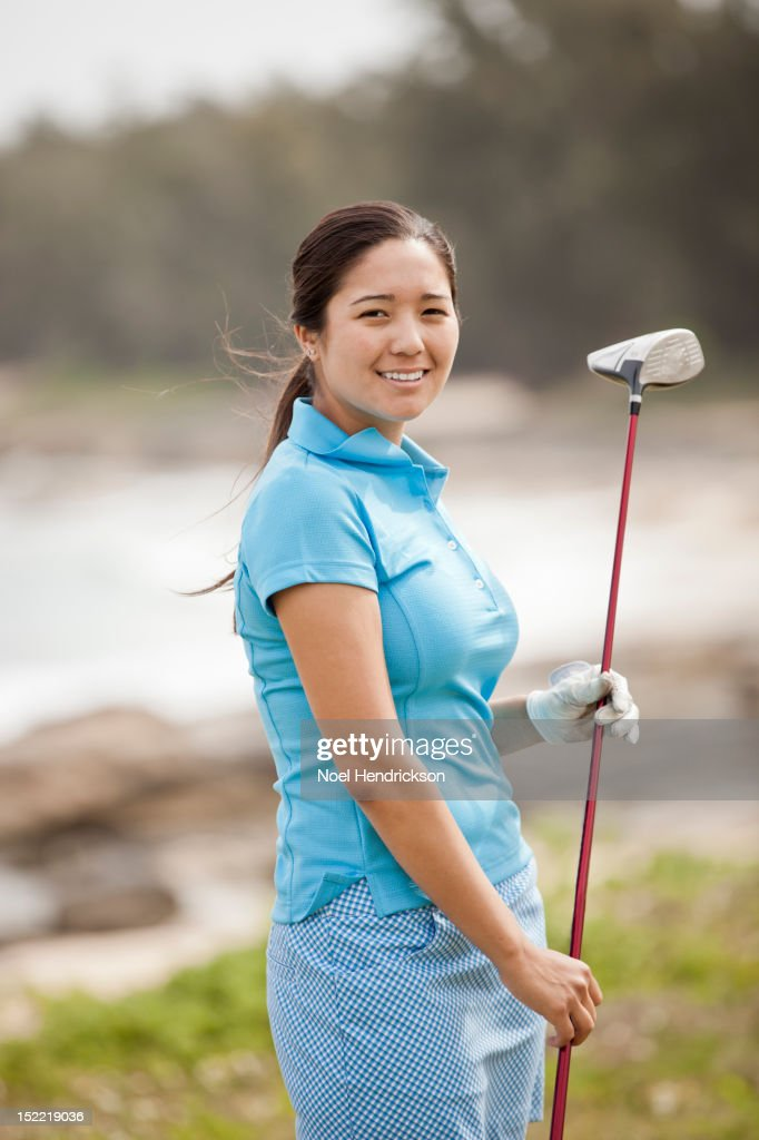 A young female golfer smiles on the course : Stock Photo