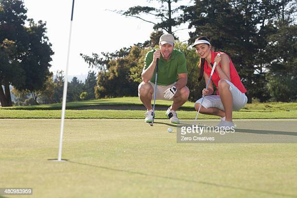 Young female golfer taking advice from trainer