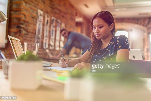 Young female graphic designer working behind a desk