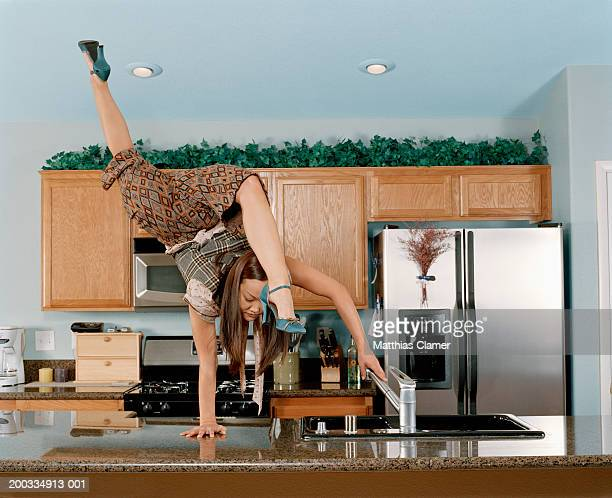 Young female gymnast doing handstand at kitchen sink