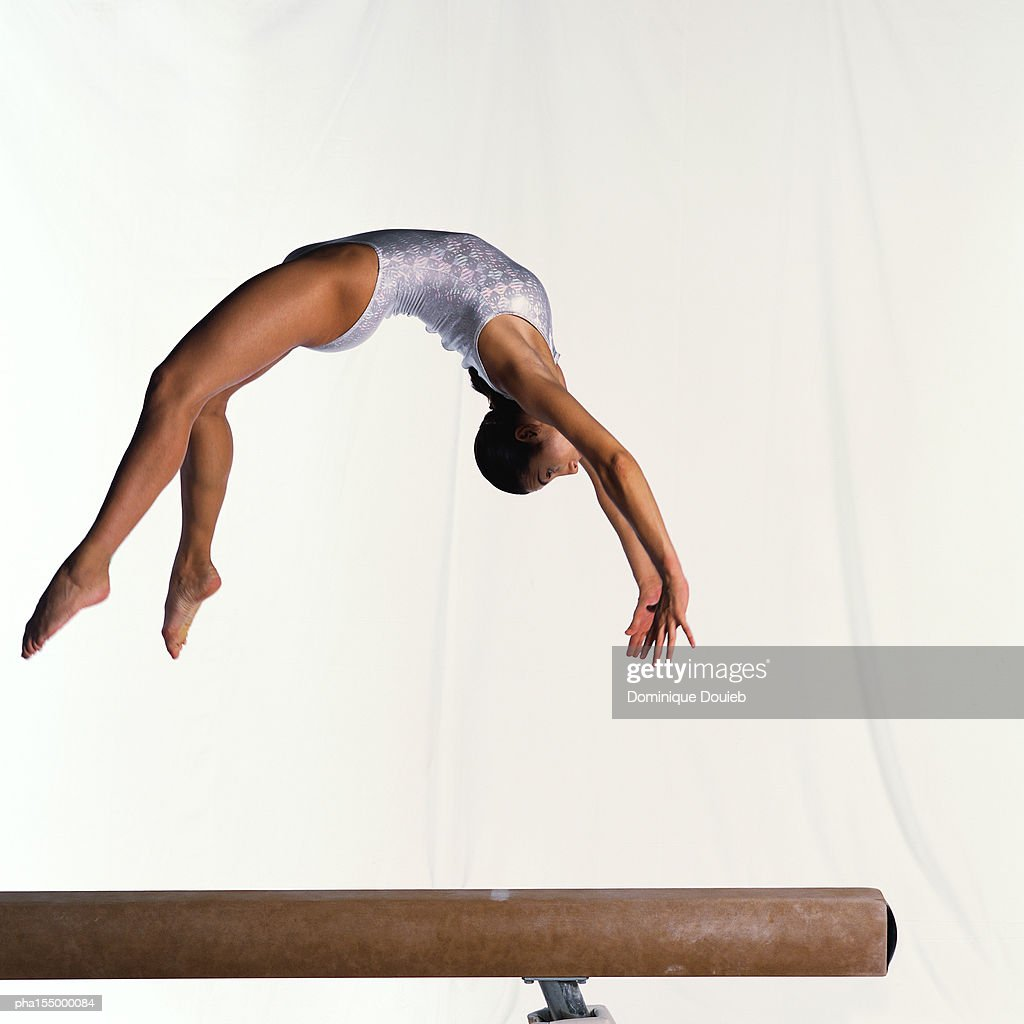 Young female gymnast on balance beam performing exercise, mid-flight, side view. : Stock Photo