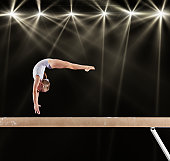 Young female gymnast on balance beam