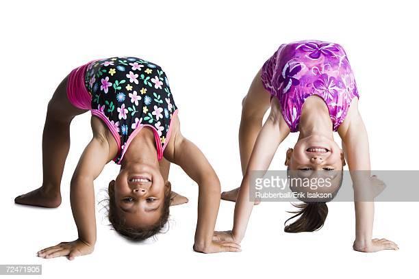 Young female gymnasts bending backwards