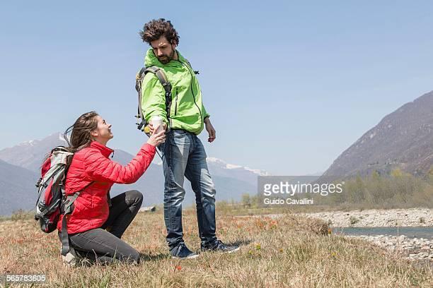 Young female hiker handing water bottle to boyfriend, Vogogna, Verbania, Piemonte, Italy