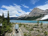 A young female hiker hiking along the Berg Lake Trail, in Mount Robson Provincial Park, British Columbia, Canada.  Mount Robson looms in the distance on a beautiful summer day with pure blue sky.