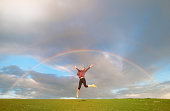 Young female hiker jumping mid air below rainbow