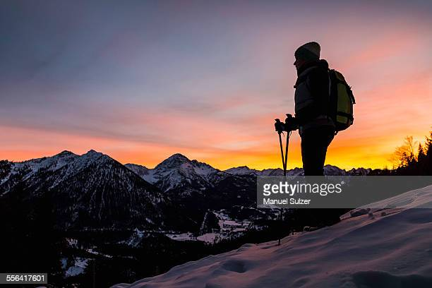 Young female hiker looking out from mountainside at dusk, Reutte, Tyrol, Austria