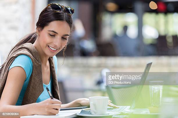 Young female Hispanic millennial studies at an outdoor cafe