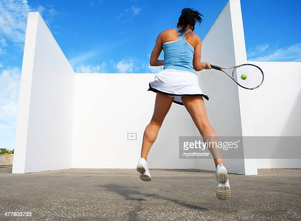 young female hitting tennis ball against a wall