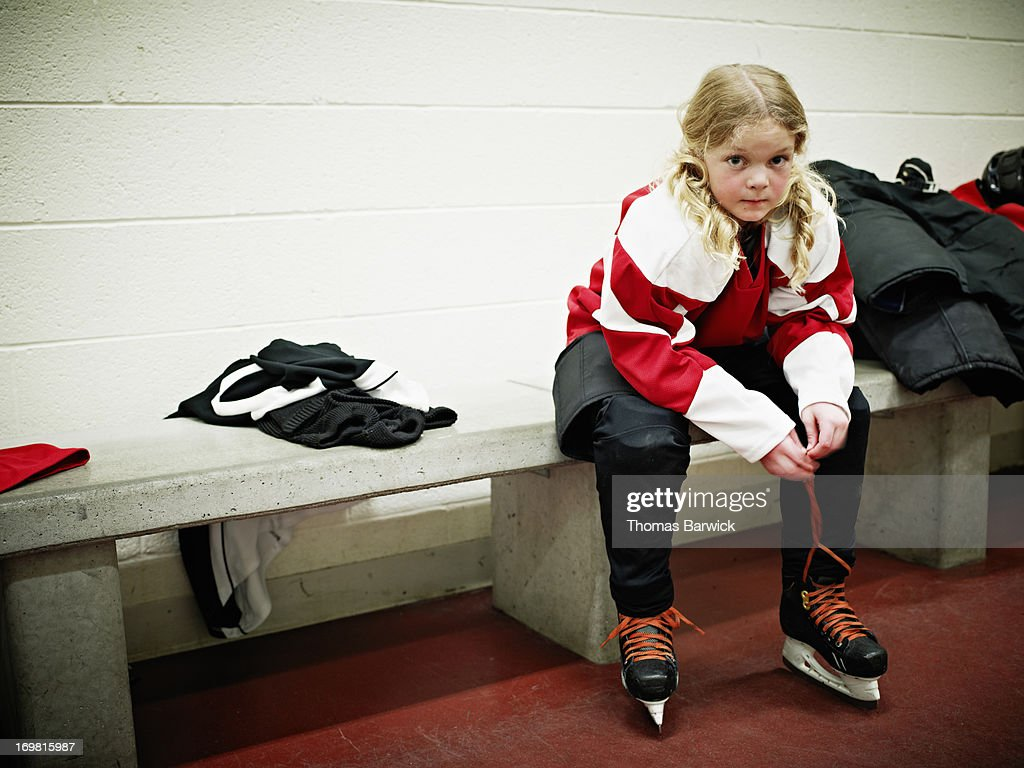Young female hockey player in locker room : Stock Photo