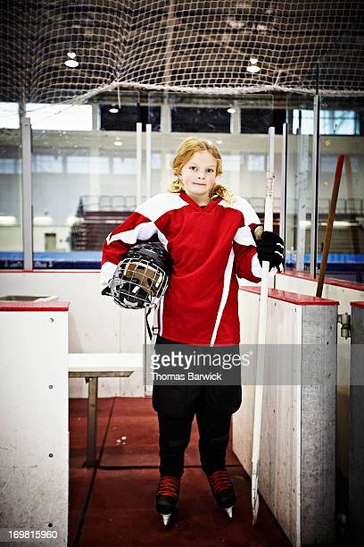 Young female hockey player standing in players box