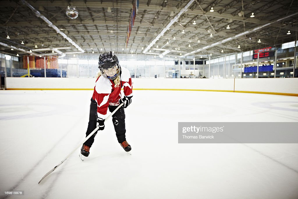 Young female hockey player standing on ice
