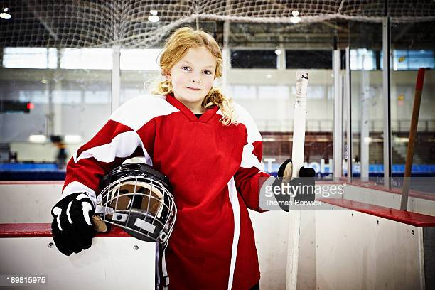 Young female ice hockey player in players box