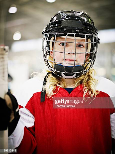 Young female ice hockey player wearing helmet