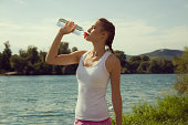 Young female jogger drinking bottled water