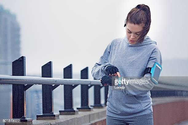 Young female jogger preparing in the city in winter