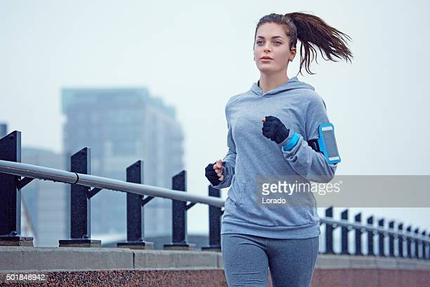 Young female jogger running in the city in winter