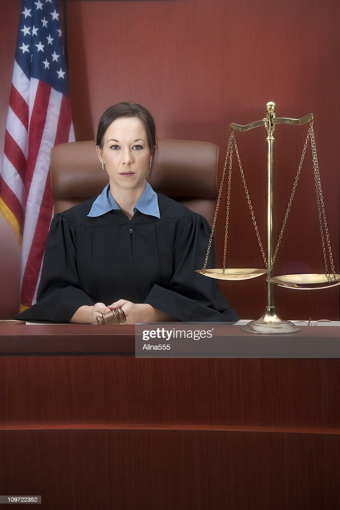 Young female judge at the bench with scales, gavel, flag : Stock Photo