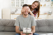 Young female keeps eyes closed to his boyfriend at home, while he is sitting on sofa with gift box, celebrating birthday
