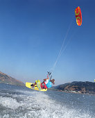 Young female kiteboarder in mid-air, rear view