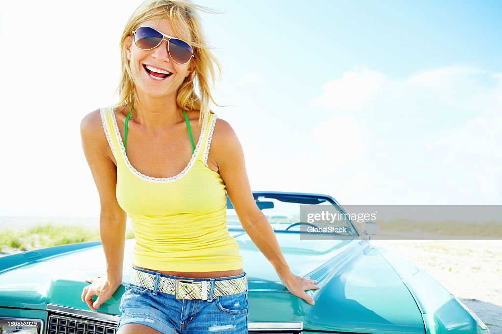 Young female leaning against convertible car on a sunny day