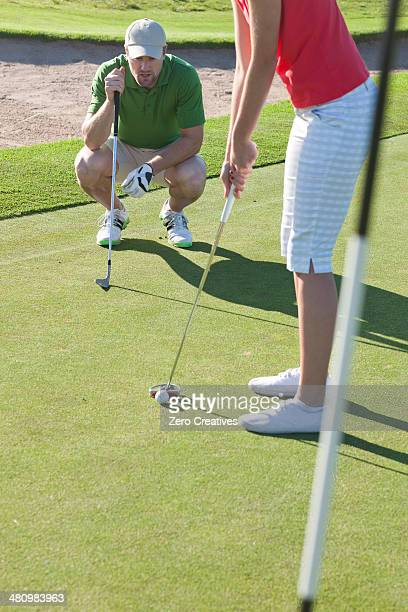 Young female lining up golf ball with trainer