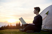 Young female looking away thoughtfully using her laptop outdoors while camping sitting near her tent dreaming achievement success travel online connection