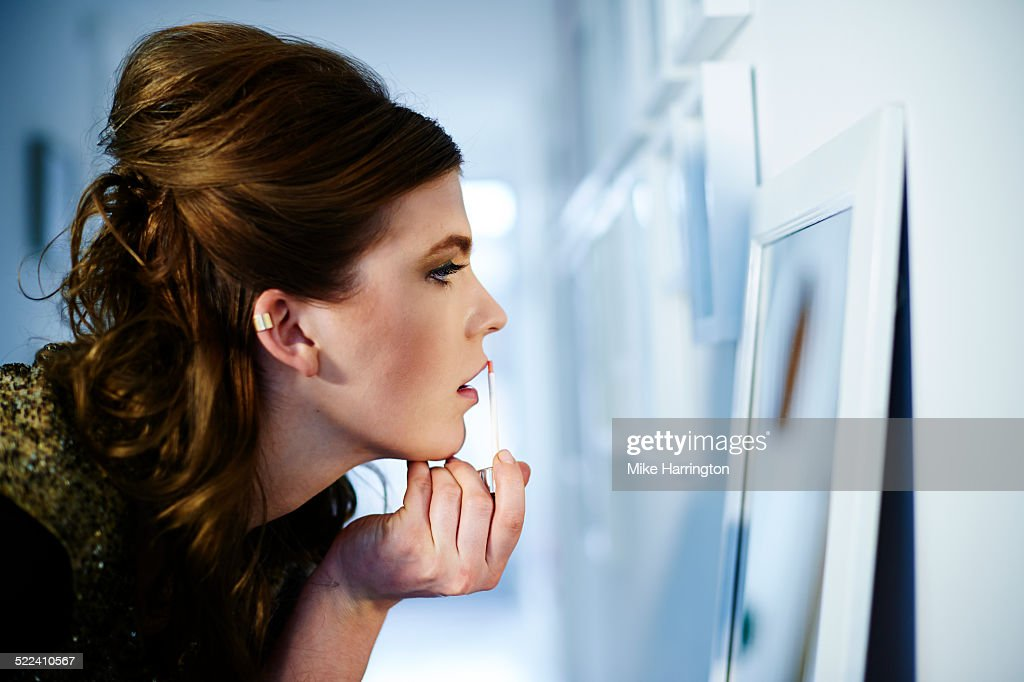 Young female looking into mirror, applying make-up : Photo