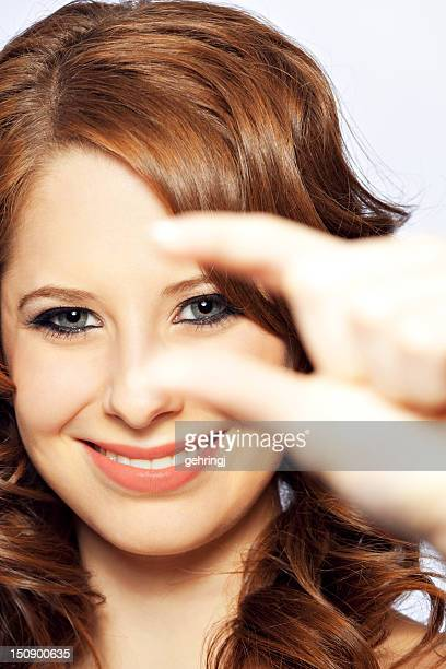 Giovane donna guardando attraverso le sue dita