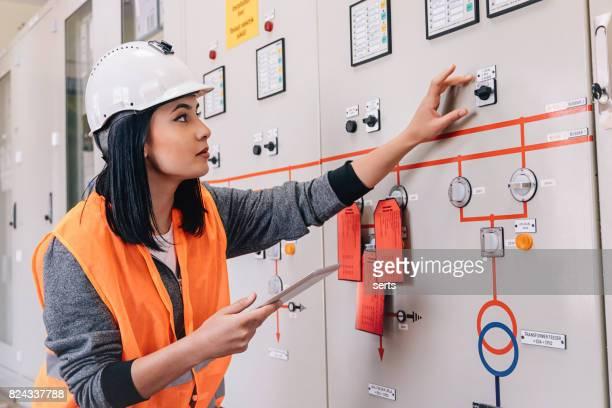 Ingénieur maintenance femelles jeunes travaillant dans la salle de contrôle de l'énergie