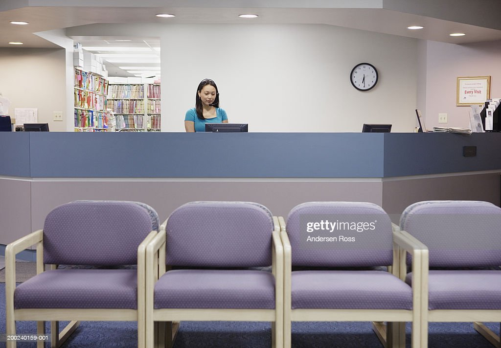 Young female medical assistant working at counter in waiting room : Stock Photo