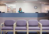 Young female medical assistant working at counter in waiting room